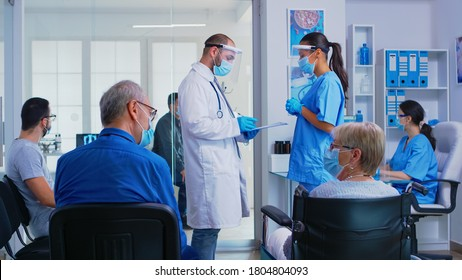Medical team with face mask against coronavirus discussing in hospital waiting room about patient diagnosis. Senior man talking with disabled woman in wheelchair. Patient waiting for examination.