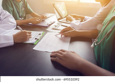 medical team having a meeting with doctors in white lab coats and surgical scrubs seated at a table discussing a patients records,success medical health care, Medicine doctor's working concept