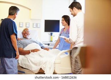 Medical Team Meeting With Senior Man In Hospital Room