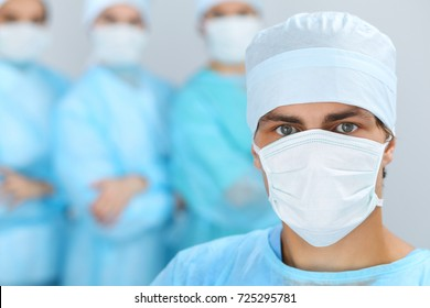Medical team performing operation. Focus at male doctor