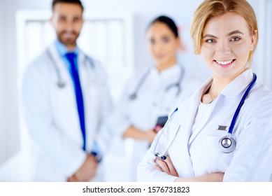 Medical team of smiling doctors, man and women inthe office, isolated on white background