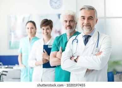 Medical team standing in line at the hospital and smiling at camera, healthcare and medical occupations concept