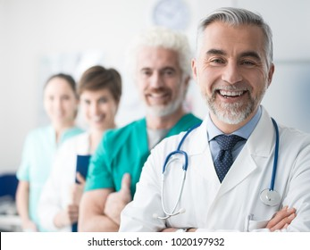 Medical team standing in line at the hospital and senior professional doctor smiling on the foreground, healthcare and teamwork concept