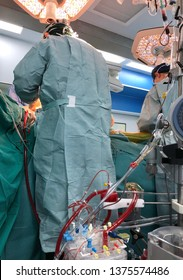 Medical team such as surgeon, scrub nurse, anesthetist and perfusionist, doing open heart surgery with cardiopulmonary bypass in operating room