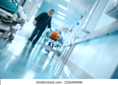 Medical team transports patient on gurney in the hospital hall, unfocused background.