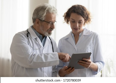 Medical team of two professional doctors talking and using digital tablet. Senior male chief physician helping young female nurse holding medical tech device discussing patient diagnosis in hospital.