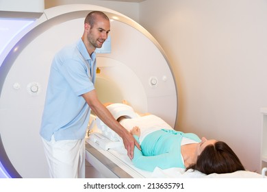 Medical technical assistant councelling patient and preparing scan of the knee with magnetic resonance tomography MRI in radiology