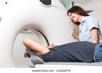 Medical technical assistant councelling patient and preparing scan of the spine with x-ray computed tomography CT  in radiology