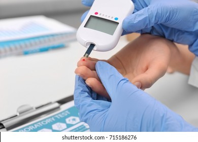 Medical technician in latex gloves testing patient's glucose level with digital glucometer in hospital