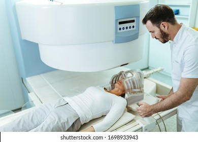 Medical technician preparing his patient who is undergoing for brain MRI san examination in the hospital.