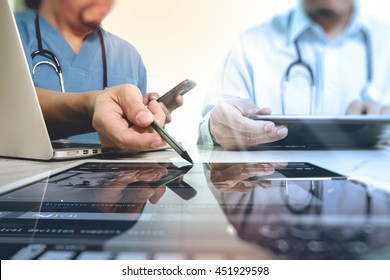 Medical technology network team meeting concept. Doctor hand working with smart phone modern digital tablet and laptop computer with graphics  chart interface, Sun flare effect photo