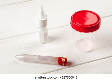 Medical tests containers on a white wooden table