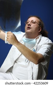 Medical theme - serious doctor examining an x-ray. Studio shot. Blue background.