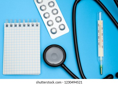 Medical thermometer and phonendoscope with pills in blister on a blue desk in the therapist's office. Medical concept of cold and flu.