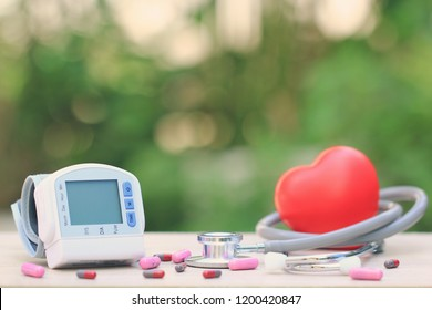 Medical tonometer for measuring blood pressure with stethoscope and red heart on green background, Medical expenses and Health care concept