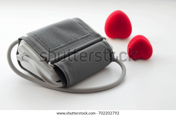 medical tonometer and red hearts on a white background
