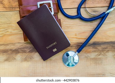 Medical tourism concept. Stethoscope with passport on wooden table.