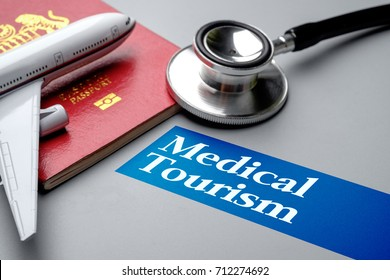 Medical Tourism, medical travel concept. Stethoscope, toy plane and passport on grey background. Selective focus image.