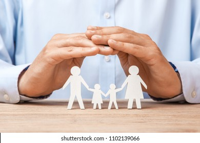 Medical or travel insurance. Man covers the family with his hands from his father, mother, son and daughter