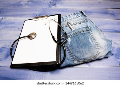 Medical treatment. Medicine concept. Medical help and consultation. Doctors attributes. Medical insurance. Phonendoscope and paper tablet on jeans background copy space. History of the disease.