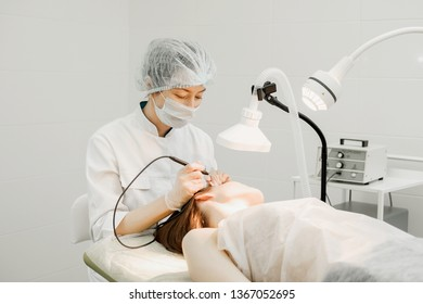 Medical treatment removal of birthmark from female patient's face. Female dermatologist surgeon using a professional electrocautery for removing mole. Radio wave electrocoagulation remove method
