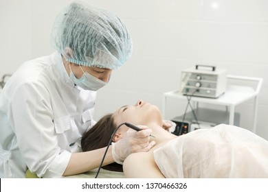 Medical treatment removal of birthmark from female patient's neck. Female dermatologist surgeon using a professional electrocautery for removing mole. Radio wave electrocoagulation remove method