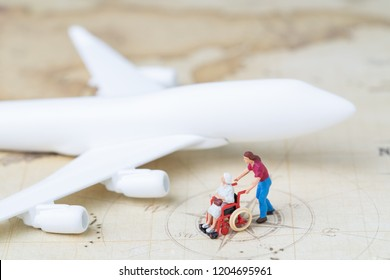 Medical trip planning or travel concept, miniature senior elderly people on wheelchair with son or caregiver standing with toy airplane on vintage world map with compass, next destination.