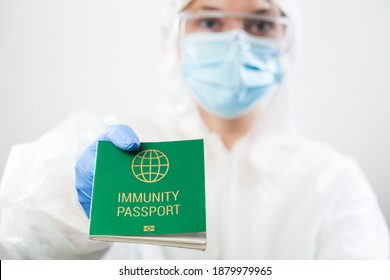 Medical UK healthcare security officer worker in personal protective equipment holding green immunity passport ID card,risk free certificate document concept,health record proof of patient recovery