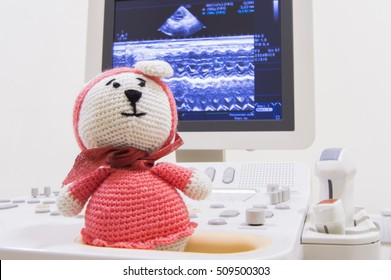 Medical ultrasound scanner and children toy knitted bunny on screen background with waves ECHO heart test or scan and ultrasonic probes. Concept photo for ultrasound examination of child in pediatrics
