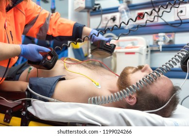 Medical urgency in the ambulance. Emergency doctor using defibrillator