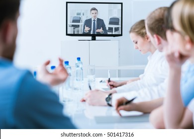 Medical video conference in a bright, blurry conference room, with a tv screen in the middle