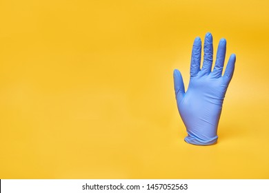 Medical vinyl, latex or nitrile glove on yellow background.