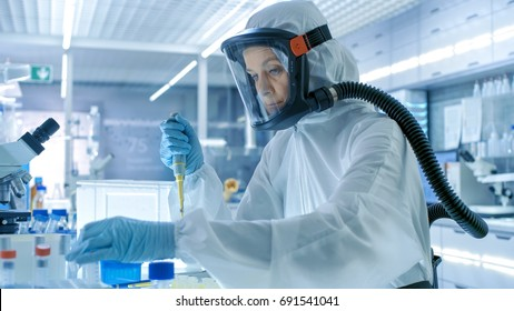 Medical Virology Research Scientist Works in a Hazmat Suit with Mask, She Takes out Test Tubes from Refrigerator Box. She Works in a Sterile High Tech Laboratory/ Research Facility.