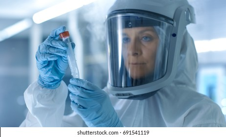 Medical Virology Research Scientist Works in a Hazmat Suit with Mask, Inspects Test Tube with Isolated Virus String from Refrigerator Box. She Works in a Sterile High Tech Laboratory Facility.