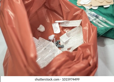 Medical waste syringe and cotton ball in plastic disposal bag after used for vaccination background.