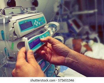 Medical worker configures equipment in ICU.
