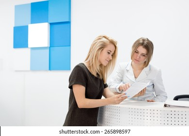 Medical worker consults patient in the central bright and white hall of the hospital. Patient beautiful young blond woman standing near the reception and holding a brochure.