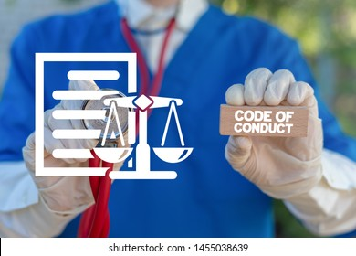 Medical worker holding wooden block with code of conduct collocation and touching document sheet with scales icon. Code of conduct health care concept.