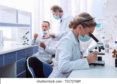 Medical worker in lab coat and sterile mask, doing a microscope analysis while her colleague are working behind