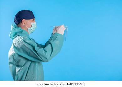 Medical worker in a mask for protection against viruses puts on gloves