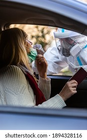 Medical worker performing drive-thru COVID-19 test, taking nasal swab sample from female patient through car window, PCR diagnostic, doctor in PPE holding test kit. She is holding passports.