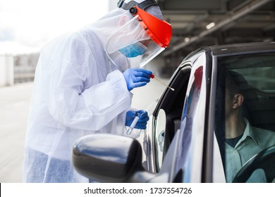 Medical worker in PPE performing nasal  throat swab on person in vehicle through car window,COVID-19 mobile testing centre,drive through facility parking lot,specimen collection and rt-PCR diagnostic