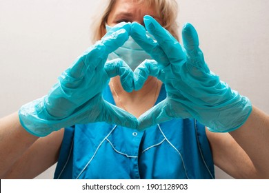 Medical worker wearing a medical mask and gloves making a heart with her hands. Support sign during pandemic