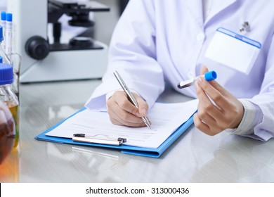 Medical worker writing results of blood test into medical card of the patient
