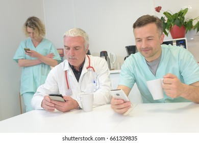 Medical workers on a break, looking at their cellphones