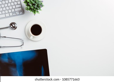 Medical workplace with stethoscope,cup of coffee,keyboard and x-ray film on white desk.Top view with copy space.
