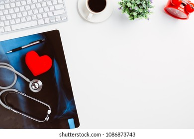 Medical workplace with stethoscope,heart,pen,keyboard,coffee cup and x-ray film on white desk.Top view with copy space.
