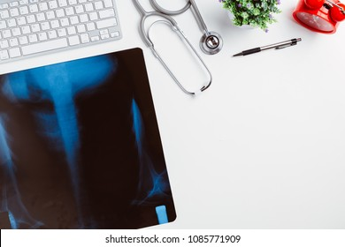 Medical workplace with stethoscope,pen,keyboard and x-ray film on white desk.Top view with copy space.