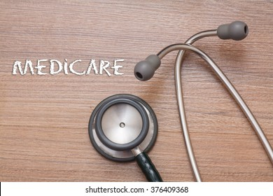 Medicare concept : stethoscope on note book with wood background