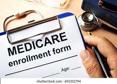 Medicare enrollment form in a hand.
